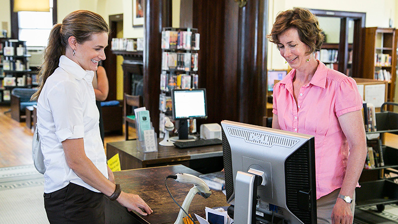 smiling librarian helping a patron at the old West branch