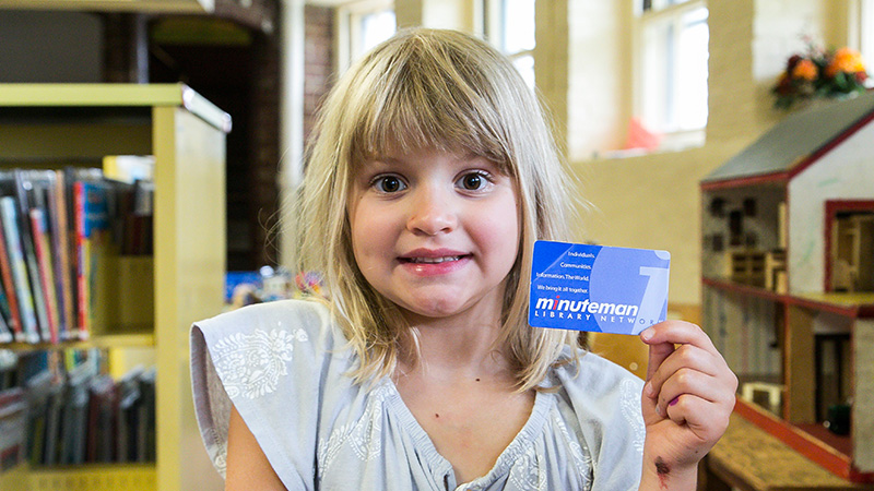 Image depicting a child holding up a library card.