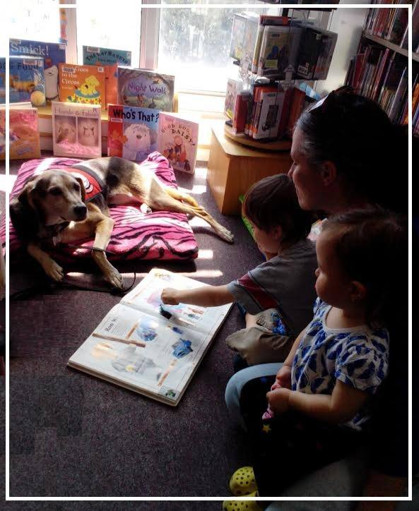Image depicting a child seated next to her mother while reading to a service dog.