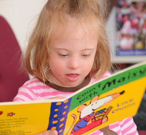 little girl reading a board book