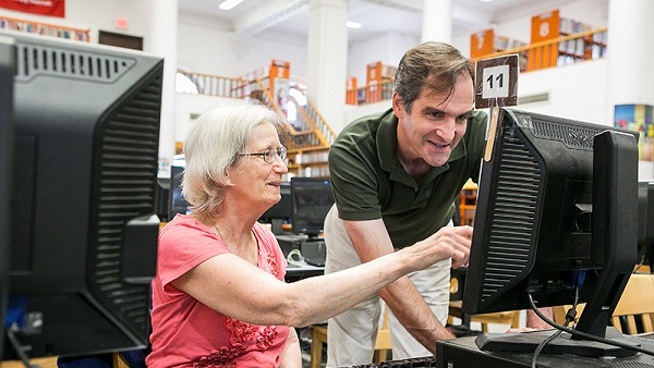 librarian instructing patron in computer use