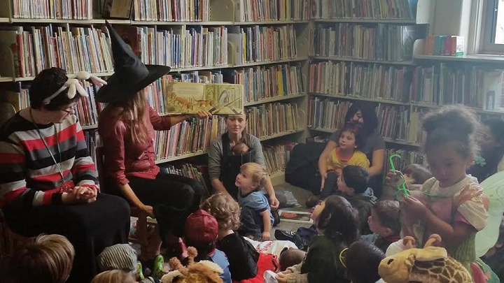 Librarian giving story time to children's group