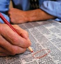 man's hand holding red pencil, circling help wanted ad in newspaper
